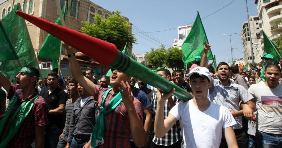 29.ago.2014 - Palestino carrega foguete de papelão em protesto em apoio ao Hamas, na cidade de Hebron, na Cisjordânia. Sete semanas de combates entre Israel e Hamas na faixa de Gaza deixaram mais de 2,1 mil mortos, cidades em ruínas e dezenas de milhares de desalojados