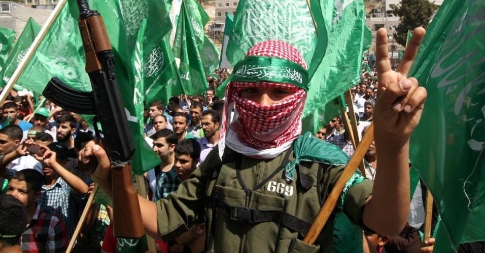 29.ago.2014 - Palestino faz sinal da vitória em protesto em apoio ao Hamas, na cidade de Hebron, na Cisjordânia. Sete semanas de combates entre Israel e Hamas na faixa de Gaza deixaram mais de 2,1 mil mortos, cidades em ruínas e dezenas de milhares de desalojados