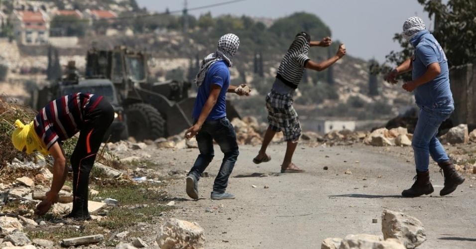 29.ago.2014 - Palestinos arremessam pedras contra forças de segurança de Israel em Kfar Qaddum, próximo à cidade de Nablus, na Cisjordânia. Um protesto ocorreu em apoio à resistência palestina na faixa de Gaza . Sete semanas de combate na região deixaram mais de 2,1 mil mortos, cidades em ruínas e dezenas de milhares de desalojados