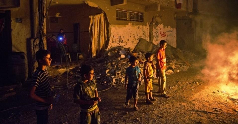 30.ago.2014 - Crianças palestinas brincam em torno de uma fogueira acesa em uma rua no bairro de Shejahiya, em Gaza. Os moradores usam o fogo para afastar mosquitos e insetos de suas casas parcialmente destruídas
