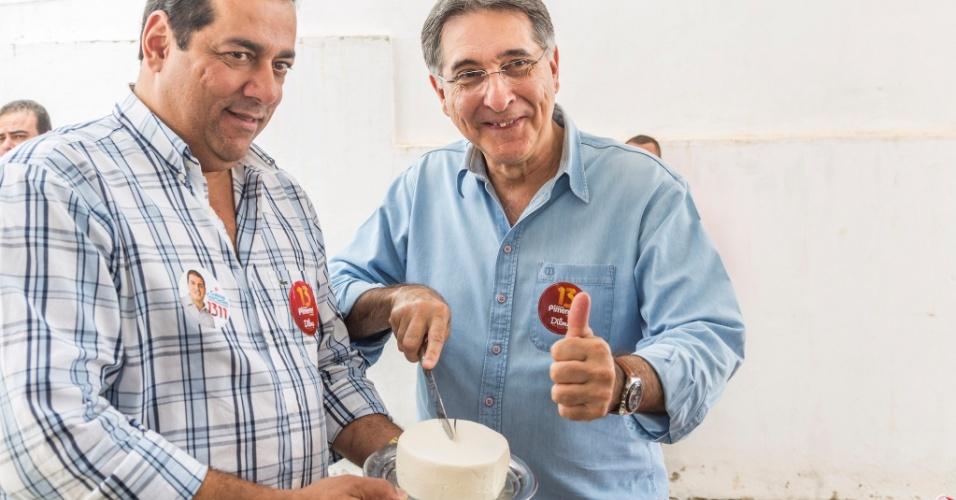 30.ago.2014 -  O candidato ao governo de Minas Gerais Fernando Pimentel (PT) posa para foto cortando queijo durante caminhada na cidade de Serro (MG)