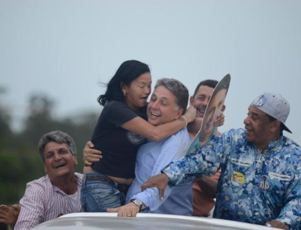 30.ago.2014 - O candidato ao governo do Rio Anthony Garotinho (PR) é abraçado por eleitora durante carreata em Sepetiba, zona Oeste do Rio de Janeiro