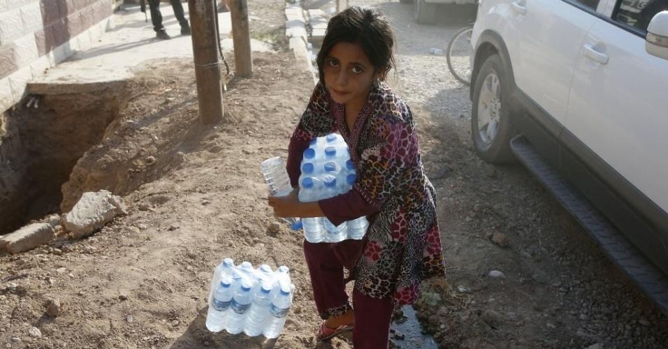 1°.set.2014 - Menina carrega garrafas de água mineral doadas por um partido político curdo após a libertação da cidade iraquiana de Amerli, que estava dominada pelo Estado Islâmico (EI), nesta segunda-feira