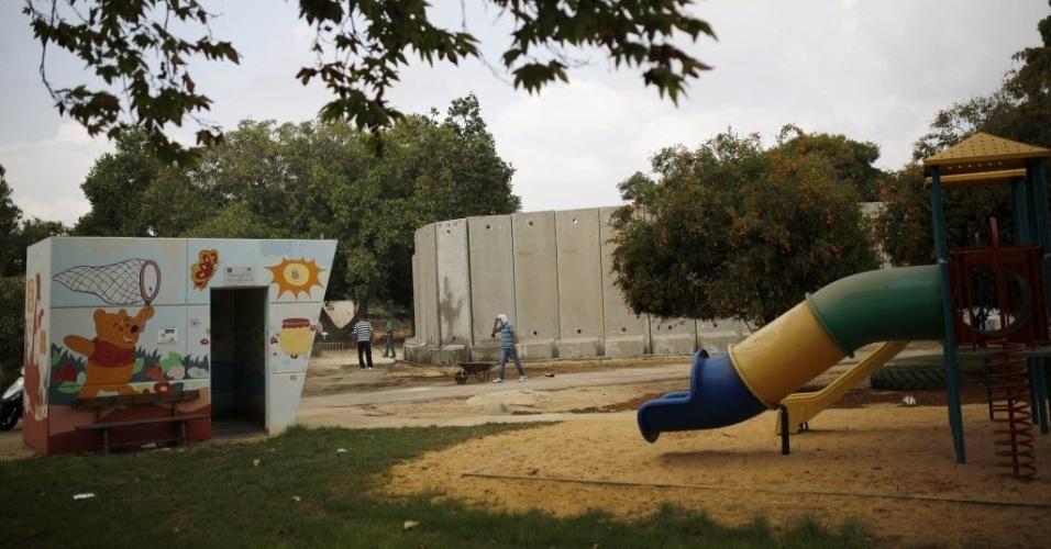 1°.set.2014 - Um parquinho de escola no kibutz de Nahal Oz, localizado na fronteira com a faixa de Gaza, em Israel, fica vazio no dia da volta às aulas. Um muro de concreto construído para proteger contra ataques de mísseis e morteiros pode ser visto ao fundo. Mesmo após o cessar-fogo nos conflitos em Gaza, acertado entre Israel e Hamas no dia 27 de agosto, muitas famílias de Nahal Oz não voltaram para casa, temendo uma retomada das tensões. No dia 22 de agosto, um menino de 11 anos foi morto no kibutz em um ataque de morteiro
