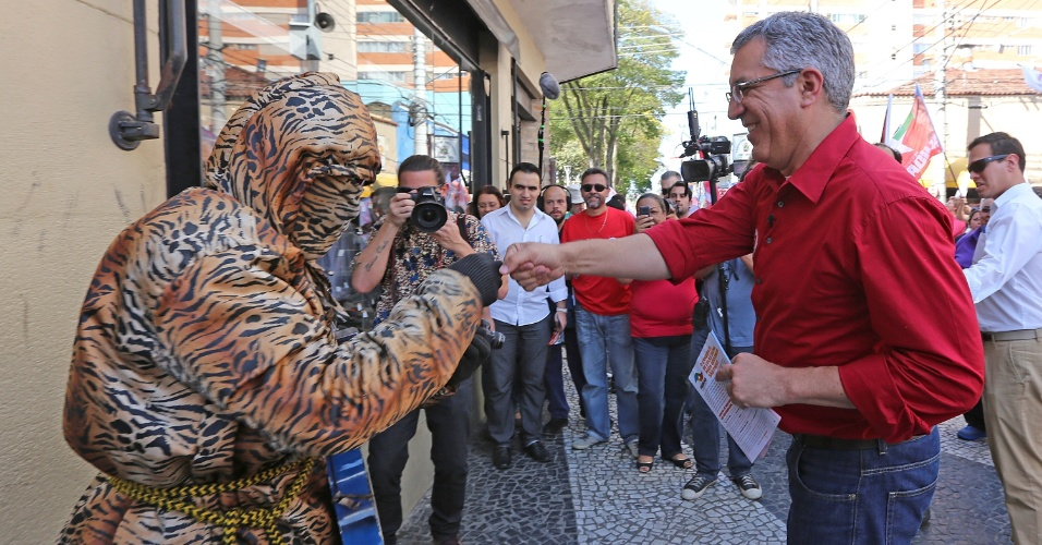 2.set.2014 - O Candidato ao governo de São Paulo pelo PT, Alexandre Padilha, fala com eleitor fantasiado de trigre, durante caminhada em Caçapava, no interior do Estado