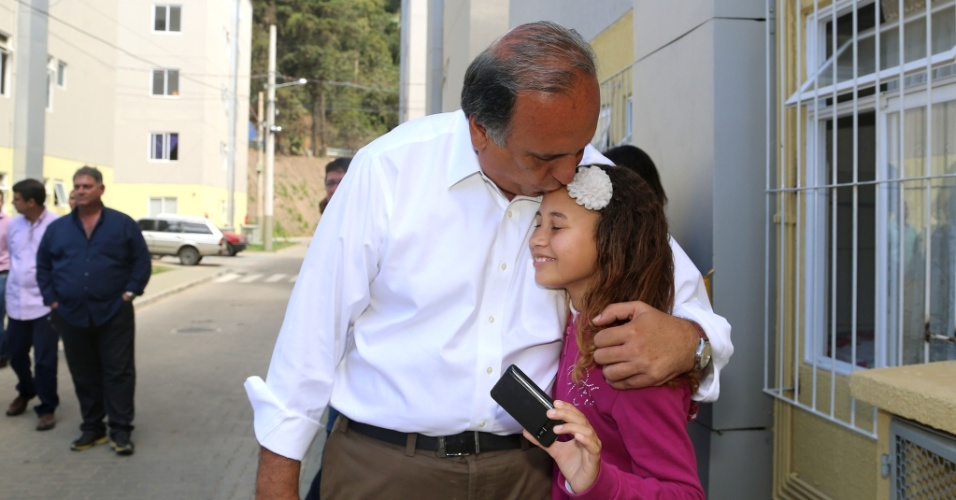 3.set.2014 - O candidato à reeleição ao governo do Rio, Luiz Fernando Pezão (PMDB), beija menina durante visita ao condomínio Terra Nova 5, em Nova Friburgo