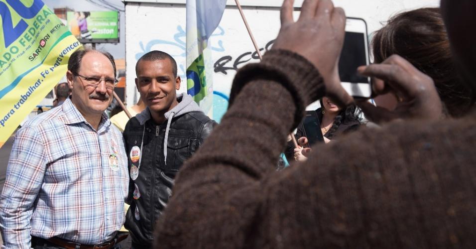 3.set.2014 - O candidato ao governo do Rio Grande do Sul pelo PMDB, Ivo Sartori, tira foto com eleitor durante caminhada no bairro de Azenha, em Porto Alegre