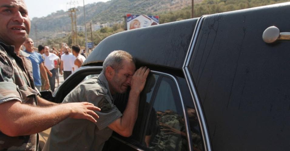 3.set.2014 - Pai de soldado libanês, capturado e morto por radicais islamitas sírios, chora ao lado de carro fúnebre carregando o caixão de um outro soldado que foi decapitado por militantes do EI (Estado Islâmico) no Arsal, durante seu funeral em Qalamoun, em Akkar