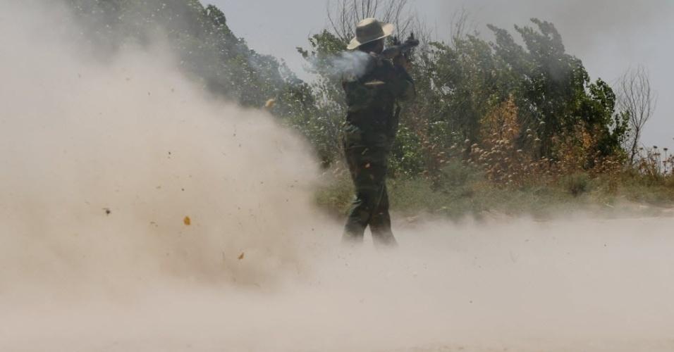 4.set.2014 - Combatente curdo dispara contra um veículo do Estado Islâmico (EI) durante confrontos na linha de frente na vila Buyuk Yeniga