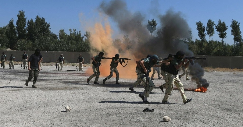4.set.2014 - Combatentes rebeldes demonstram habilidade com as armas durante uma exibição militar, como parte de uma cerimônia de formatura em um acampamento no leste da al Ghouta, perto de Damasco, na Síria. Os combatentes rebeldes recém-formados, que passaram por treinamento militar, irão se juntar a brigada