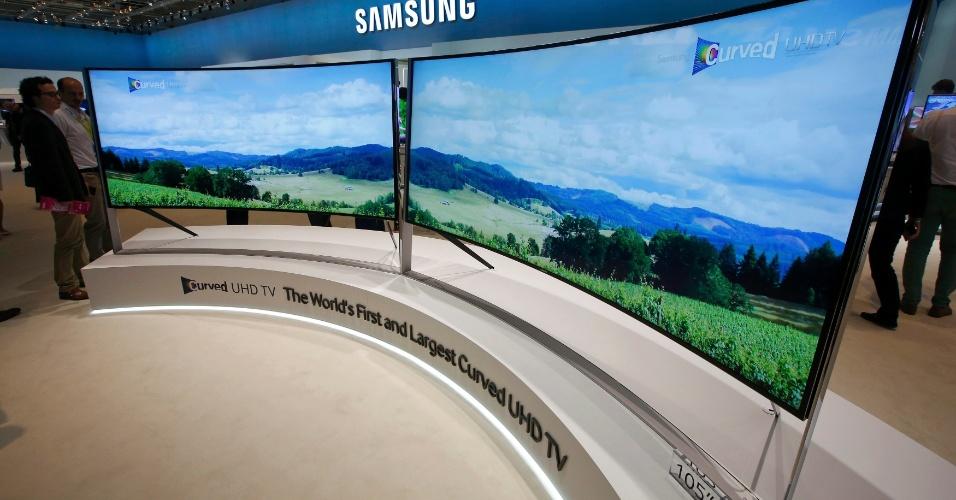 4.set.2014 - Além de possuir uma tela gigante de 105 polegadas, a nova UHD TV (televisor de ultradefinição) da Samsung é flexível: pode passar de plana para curva com o apertar de um botão. Isso pode melhorar a visualização das imagens,exibidas na proporção 21:9,  por telespectadores em ângulos diferentes. Embora a Samsung não tenha revelado o preço, a versão plana da TV custa US$ 120 mi (R$ 269 mil)