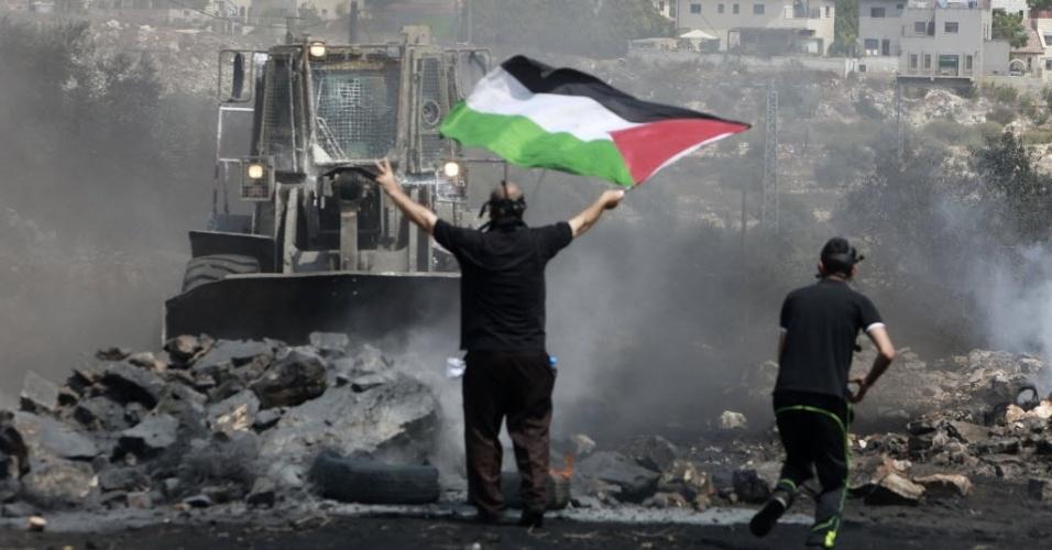 5.set.2014 - Manifestante segura bandeira palestina na frente de uma escavadeira militar israelense, durante confrontos após um protesto contra o assentamento judaico localizado perto de Qadomem, na Cisjordânia