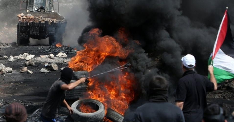 5.set.2014 - Manifestantes palestinos confrontam escavadeira militar israelense na vila de Kfar Qaddum, na Cisjordânia ocupada. Israel lançou uma licitação para a construção de 283 casas na colônia de Elkana na Cisjordânia