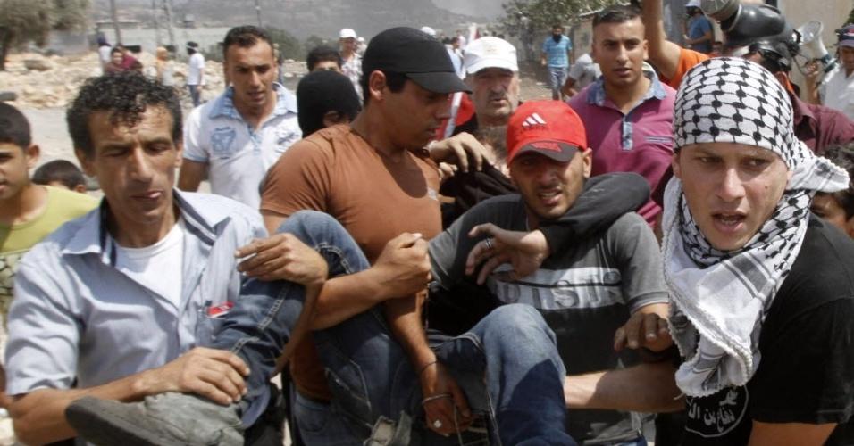 5.set.2014 - Palestinos carregam um manifestante ferido durante os confrontos com o Exército israelense, durante protesto contra o assentamento judaico perto de Qadomem, na Cisjordânia
