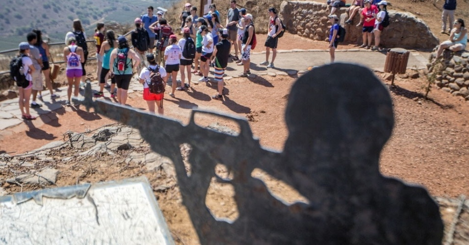 5.set.2014 - Turistas observam fumaça devido uma explosão durante combate entre membros das forças do governo sírio e os rebeldes, nas Colinas de Golã, região da fronteira entre Israel e a Síria