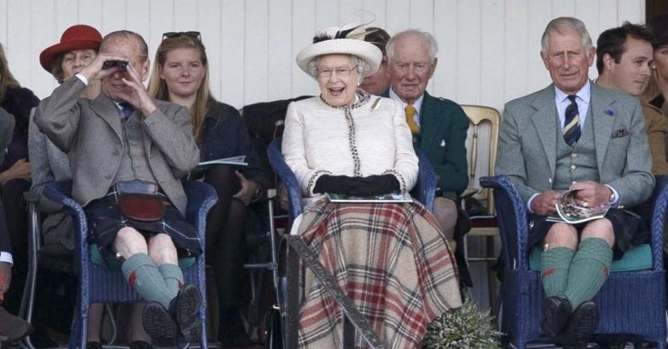 6.set.2014 - Com uma sorridente rainha Elizabeth 2ª ao centro, o príncipe Philip, Duque de Edimburgo (esq.), e o príncipe Charles (dir.), usam kilt enquanto assistem às competições do Braemar Royal Highland Gathering 2014, na cidade de Braemar, na Escócia. O evento anual, que envolve diversas modalidades de atletismo, conta com a rainha como anfitriã