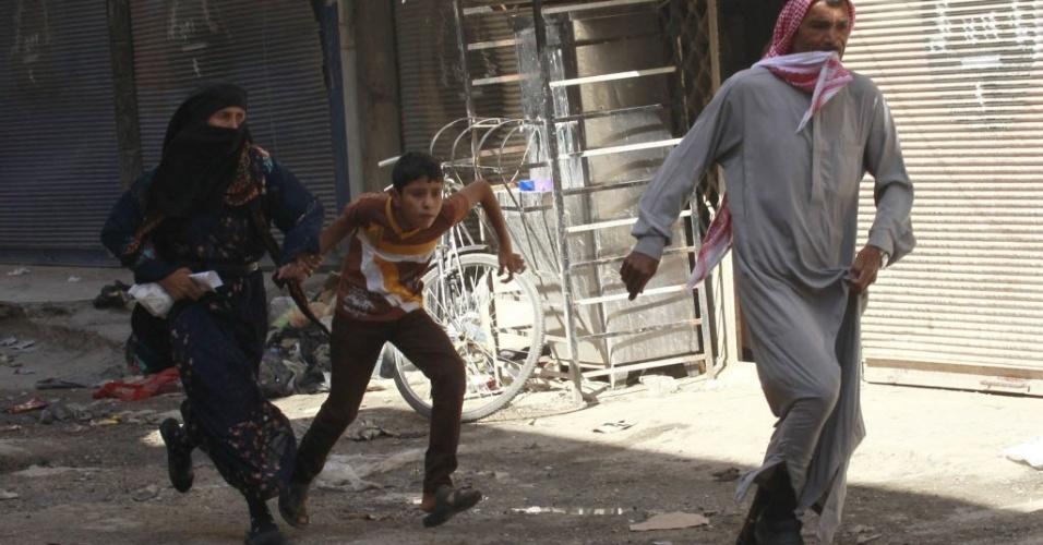 6.set.2014 - Moradores fogem durante um ataque aéreo atribuído a forças leais ao presidente da Síria, Bashar al-Assad, próximo a um mercado de rua no centro de Raqqa