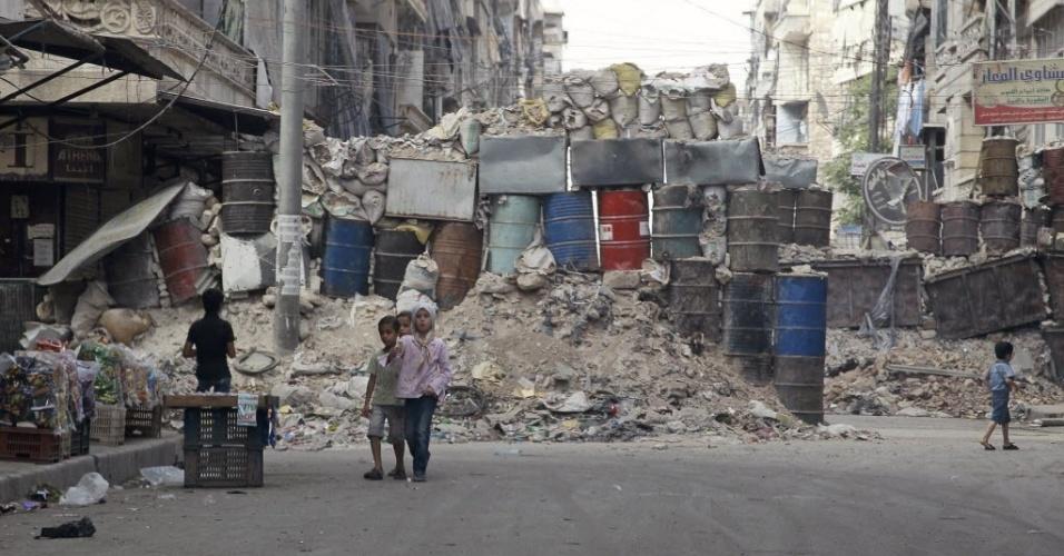 7.set.2014 - Crianças andam na frente de entulhos, barris e sacos de areia que formam uma barricada improvisada para proteção contra franco-atiradores na cidade de Aleppo, na Síria