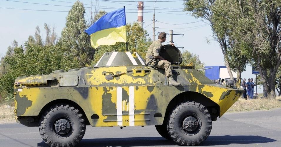 7.set.2014 - Soldado ucraniano sentado no topo de veículo militar durante patrulha na periferia da cidade portuária de Mariupol. Bombardeios abalaram a cidade durante a noite, gerando temores em relação à trégua entre o governo e separatistas pró-Rússia