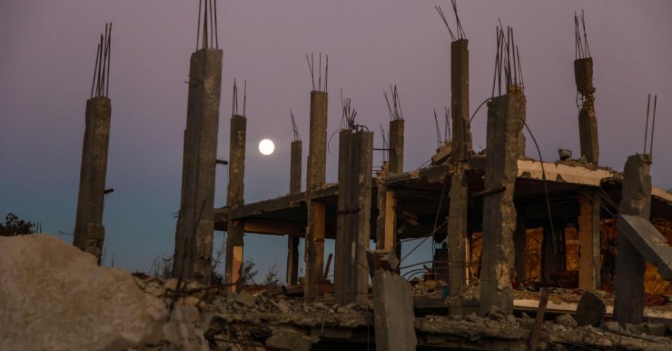 8.set.2014 - A lua cheia é vista sobre os escombros de uma casa destruída na Cidade de Gaza, na faixa de Gaza