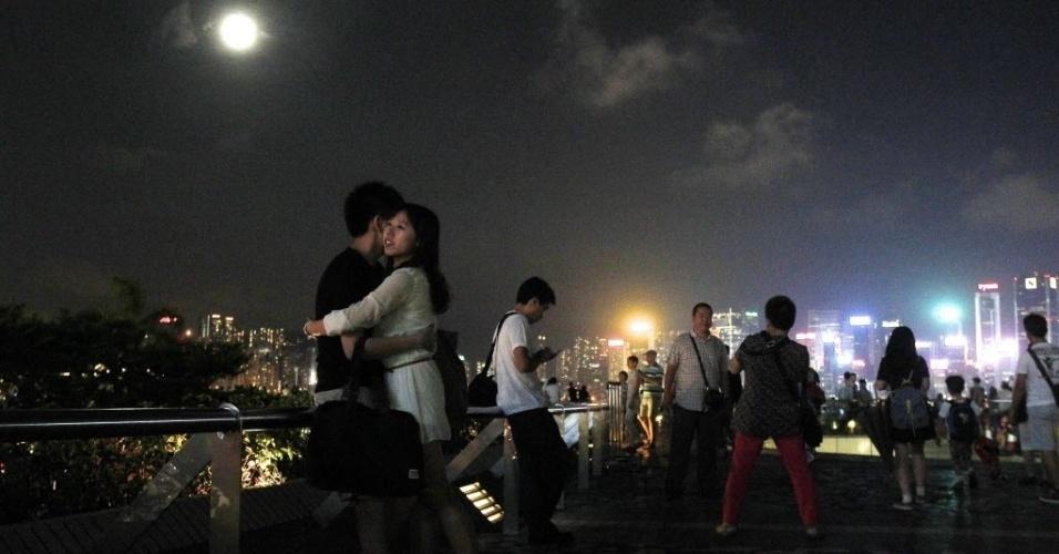 8.set.2014 - Casal se abraça sob lua cheia em fonte de água em Hong Kong, na China.Nesta segunda-feira (8) acontece o terceiro e último fenômeno da superlua de 2014. A mudança ocorre quando a lua está perto do horizonte e parece maior e mais brilhante do que a lua cheia comum. Também hoje é celebrado na China o festival de lanternas
