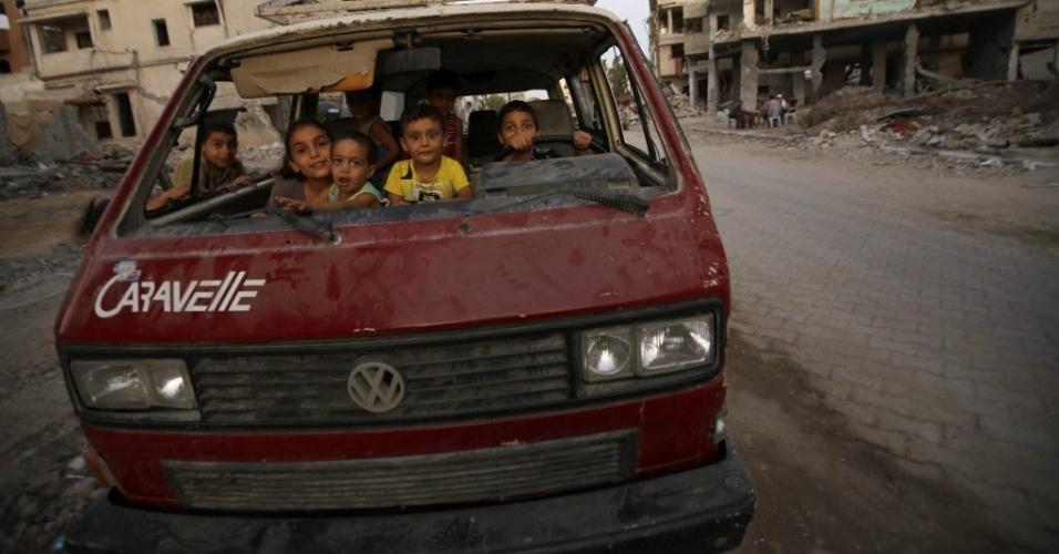 8.set.2014 - Crianças brincam em um carro destruído próximo aos destroços de casa no bairro de Al-Shejaeiya, no leste da Faixa de Gaza