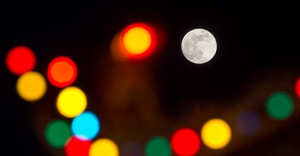 8.set.2014 - Lua cheia é fotografada entre luzes em Kuala Lumpur, na Malásia. Nesta segunda-feira (8) acontece o terceiro e último fenômeno da superlua de 2014. A mudança ocorre quando a lua está perto do horizonte e parece maior e mais brilhante do que a lua cheia comum