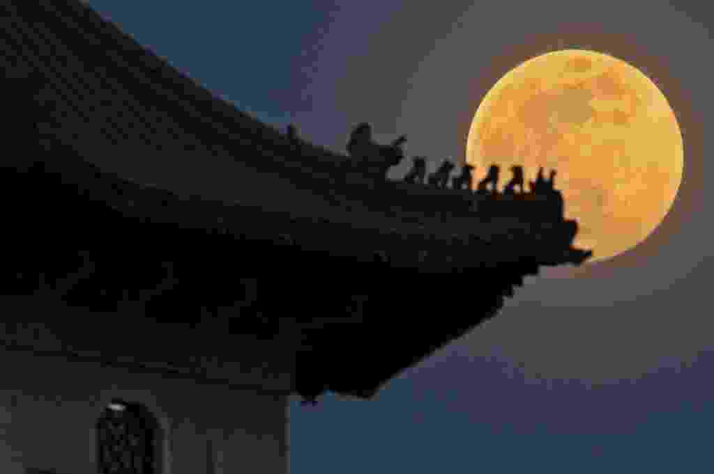 8.set.2014 - Lua cheia é fotografada sobre o jardim chinês de Cingapura. Nesta segunda-feira (8) acontece o terceiro e último fenômeno da superlua de 2014. A mudança ocorre quando a lua está perto do horizonte e parece maior e mais brilhante do que a lua cheia comum - Then Chih Wey/Xinhua