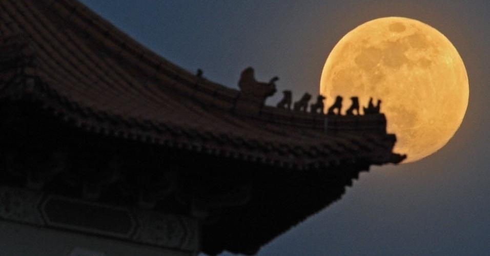 8.set.2014 - Lua cheia é fotografada sobre o jardim chinês de Cingapura. Nesta segunda-feira (8) acontece o terceiro e último fenômeno da superlua de 2014. A mudança ocorre quando a lua está perto do horizonte e parece maior e mais brilhante do que a lua cheia comum