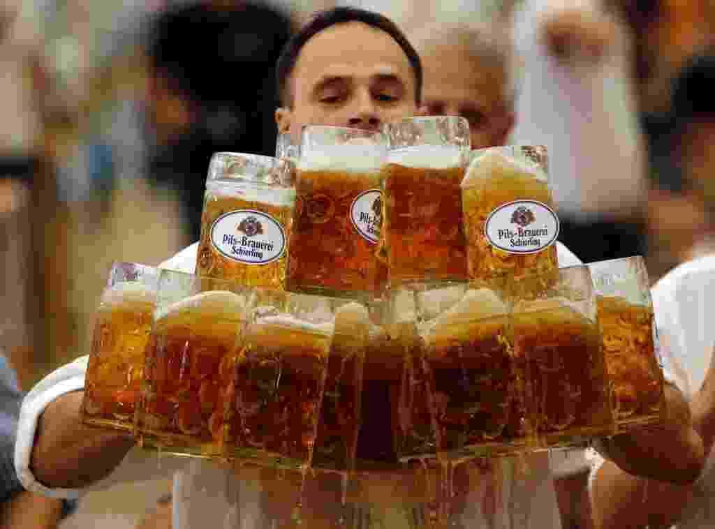 """8.set.2014 - O garçom alemão Oliver Struempfl possui o novo recorde mundial de maior quantidade de canecas de um litro de cerveja carregadas ao mesmo tempo. A busca pelo recorde mundial ocorreu em Abensberg. Struempfl conseguiu levar 27 canecas cheias ao longo de percurso de 40 metros, sem deixar nada cair. Seu feito constará agora no """"Guinness Book"""", o livro dos recordes - Michael Dalder/Reuters"""