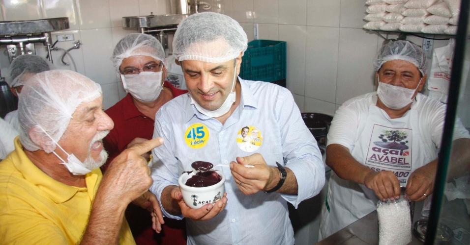 8.set.2014 - O candidato à Presidência Aécio Neves (PSDB) faz campanha em Marabá, no interior do Pará, nesta seguda-feira. Ao lado do governador paraense e candidato à reeleição, Simão Jatene (PSDB, de amarelo), Aécio come açaí