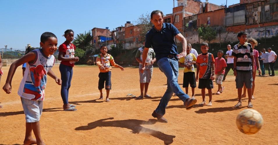 8.set.2014 - O candidato ao governo de São Paulo Paulo Skaf (PMDB) joga bola com moradores de uma ocupação em uma área da SP-Prev, no Cursino, na zona sul da capital, nesta segunda-feira