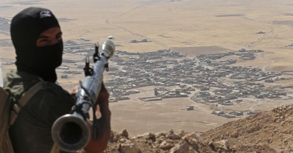 8.set.2014 - Soldado curdo segura um morteiro em posto de observação próximo à vila de Baretle, ao fundo da foto, que está sob controle do Estado Islâmico (EI), na cidade de Kazir, ao sul de Mosul, no Iraque