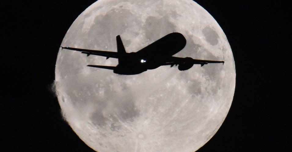 8.set.2014 - Um avião de passageiros prepara-se para pousar no Aeroporto Internacional Heathrow, em Londres, tendo ao fundo a lua cheia. Essa é a última superlua que poderá ser vista este ano