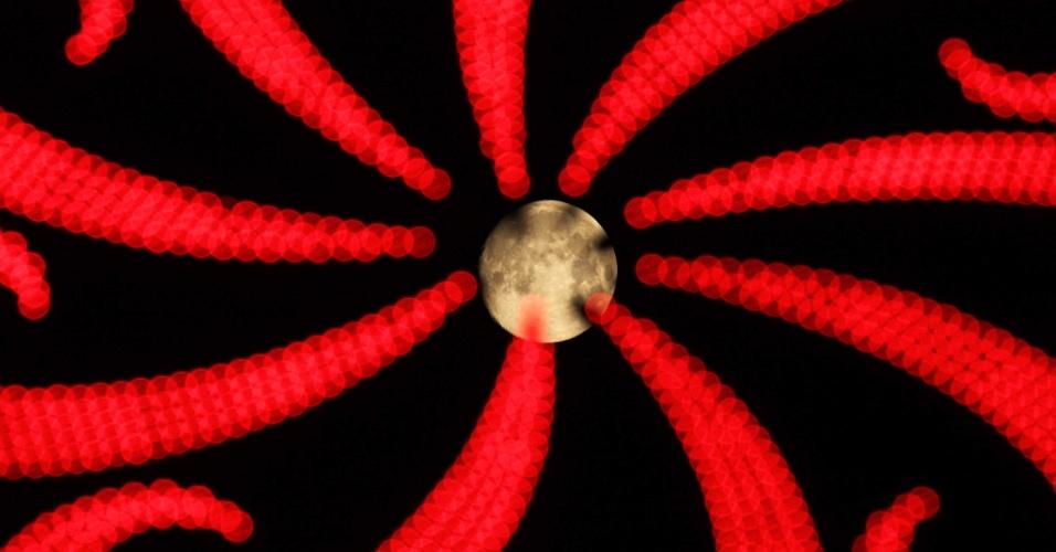 08.set.2014 - Lua vista através de cartaz luminoso de neon, na província de Jiangsu, na China. Os chineses celebram o festival da lua nesta segunda-feira (8)