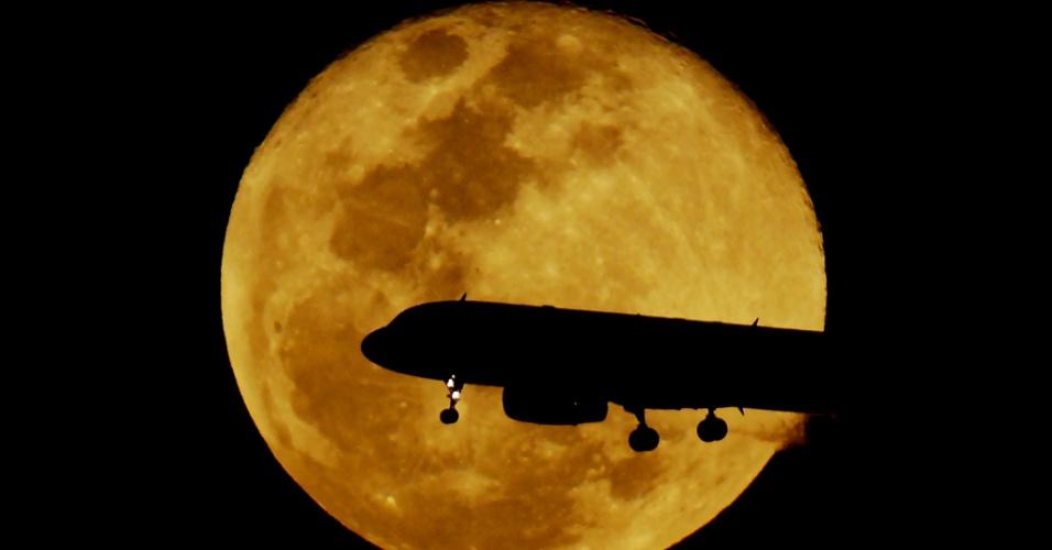 9.set.2014 - Avião se prepara para descer no aeroporto de Congonhas, na zona sul de São Paulo, na noite desta terça-feira (9). A lua cheia vista ao fundo é a última superlua do ano. O fenômeno, em que a lua parece maior e mais brilhante, pôde ser visto entre a noite de domingo e anoite desta terça-feira