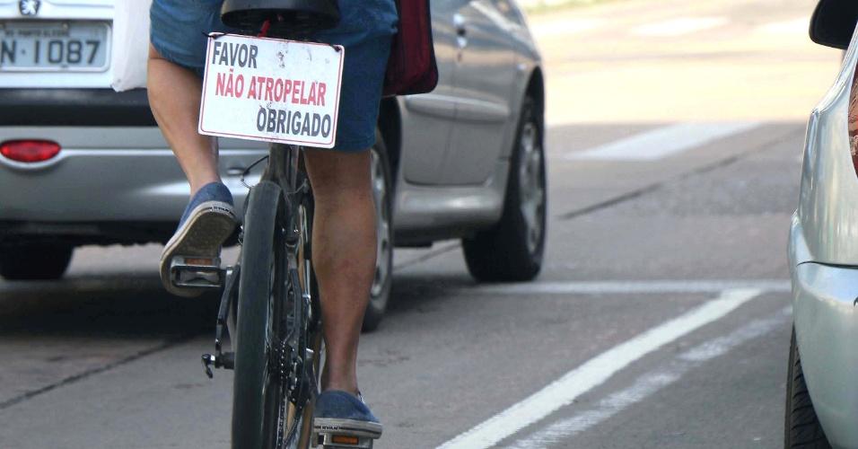 9.set.2014 - Ciclista carrega uma placa na bicicleta com os dizeres