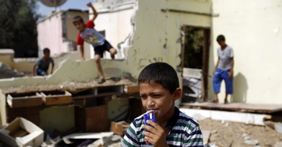 9.set.2014 - Crianças palestinas brincam perto de uma casa destruída em Bureij, campo de refugiados no centro da Faixa de Gaza, nesta terça-feira (9). A ONU e o governo palestino fizeram um apelo aos doadores internacionais para a arrecadação de US$ 550 milhões em ajuda para ajudar milhares de habitantes de Gaza afetados por uma devastadora guerra com Israel
