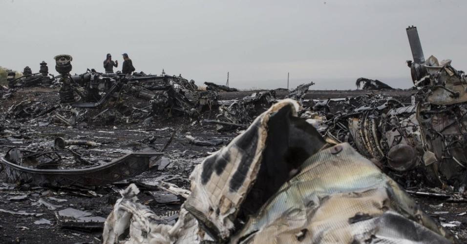 9.set.2014 - Homens conversam próximo a restos da fuselagem do voo MH17,da Malaysia Airlines, que foi abatido em julho na região de Donetsk, no leste da Ucrânia. Segundo o relatório preliminar da Junta holandesa de Segurança sobre as causas do acidente, o avião foi derrubado por uma série de