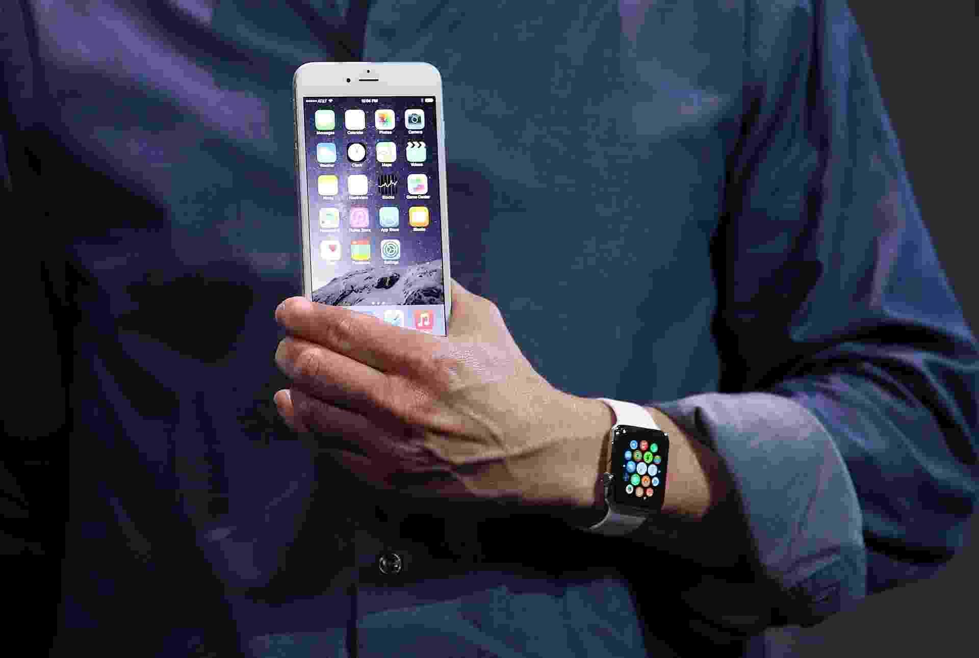 Tim Cook, diretor-executivo da Apple, segura um iPhone 6 durante apresentação do smartphone - Justin Sullivan/Getty Images/AFP