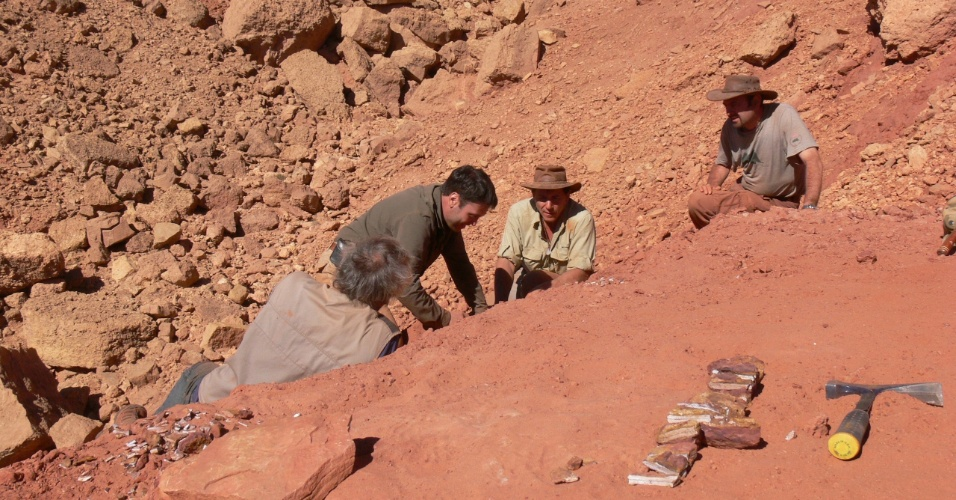 10.set.2014 - Da esquerda para a direita, paleontólogos David Martill, Nizar Ibrahim, Paul Sereno e Cristiano Dal Sasso no local de campo no Marrocos. A espinha de um Spinosaurus aegyptiacus aparece no plano. Pesquisadores descobriram que o dinossauro carnívoro, maior do que o Tyrannosaurus rex, era semiaquático, característica rara entre os dinossauros