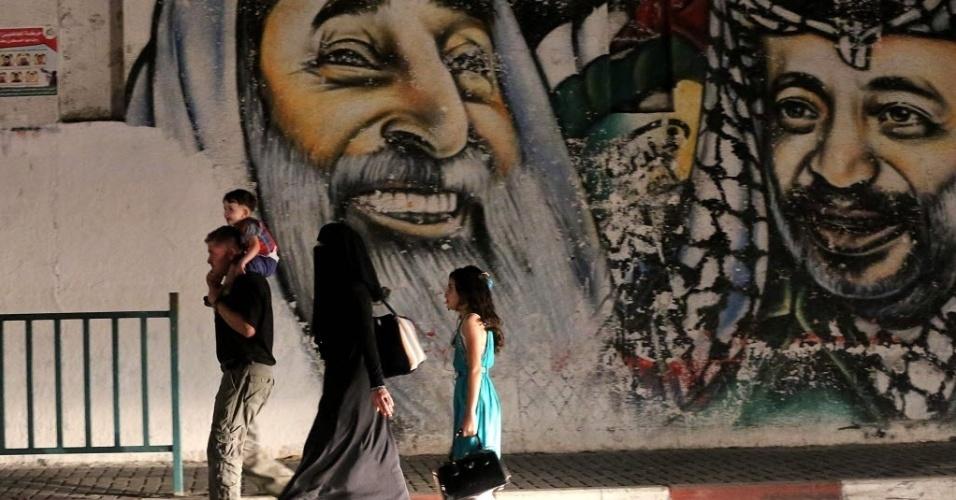 11.set.2014 - Família caminha diante de muro com imagem do líder palestino Yasser Arafat (dir.) e do líder do Hamas Sheikh Ahmad Yassin, ambos falecidos, na Cidade de Gaza. Duas semanas após um cessar-fogo nos conflitos entre Hamas e Israel, o exército israelense abriu cinco investigações criminais sobre incidentes envolvendo seus próprios militares no conflito em Gaza. Os incidentes investigados incluem bombardeios de Israel a uma escola da ONU no norte da faixa de Gaza, em 24 de julho, em que morreram 15 pessoas. Outros dois bombardeios a escolas da ONU, em 30 de julho e 3 de agosto, não foram mencionados