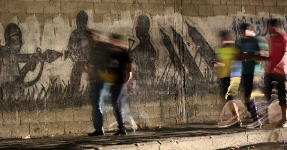 11.set.2014 - Família caminha por rua da Cidade de Gaza. Duas semanas após um cessar-fogo nos conflitos entre Hamas e Israel, o exército israelense abriu cinco investigações criminais sobre incidentes envolvendo seus próprios militares no conflito em Gaza. Os incidentes investigados incluem bombardeios de Israel a uma escola da ONU no norte da faixa de Gaza, em 24 de julho, em que morreram 15 pessoas. Outros dois bombardeios a escolas da ONU, em 30 de julho e 3 de agosto, não foram mencionados