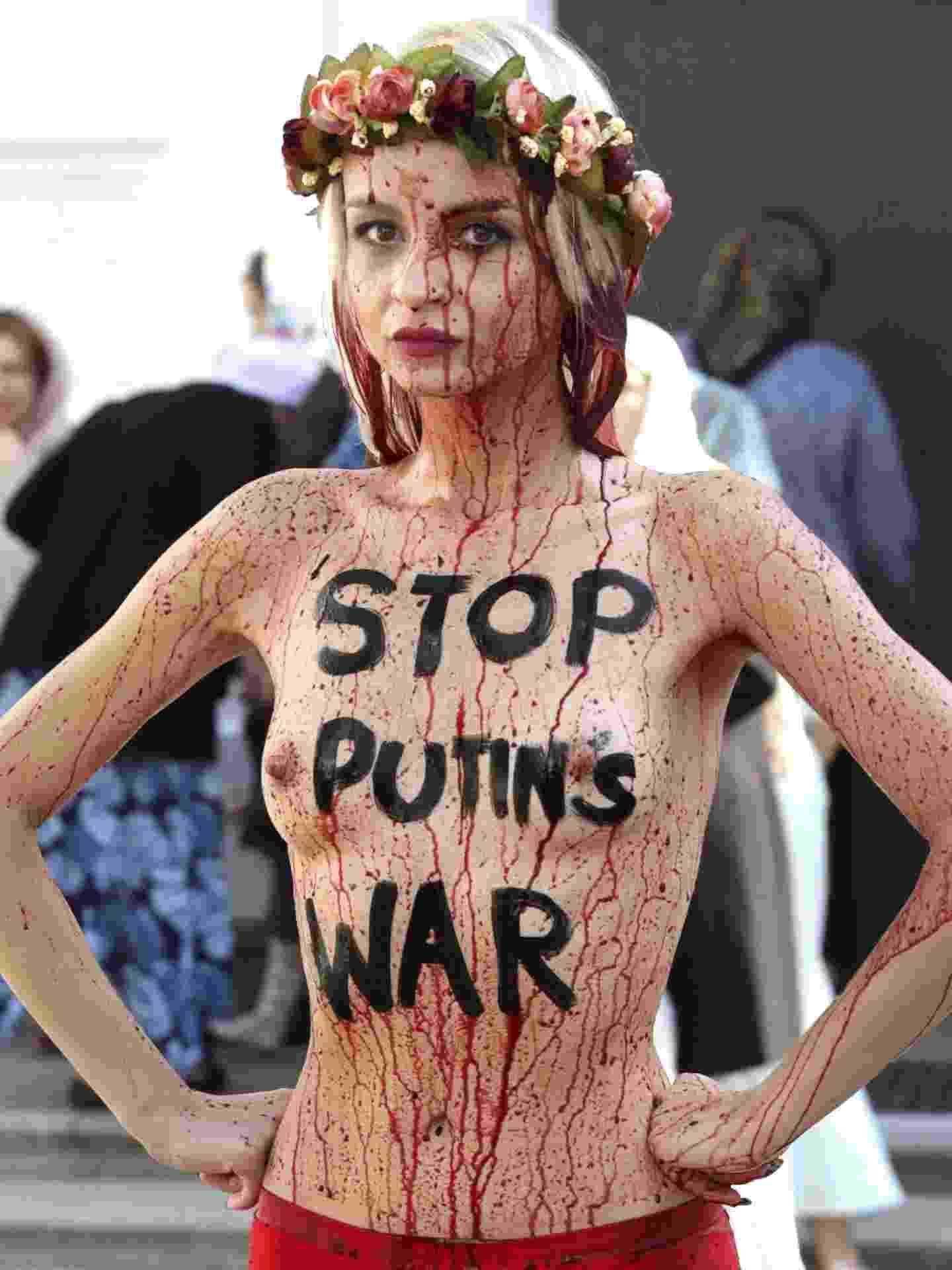 11.set.2014 - Uma ativista seminua do grupo Femen usa sangue falso durante protesto em Kiev, na Ucrânia, contra a intervenção da Rússia no país. Em seu corpo está escrito ?Pare a guerra de Putin?, fazendo menção ao presidente russo, Vladimir Putin - Tatyana Zenkovic/Efe
