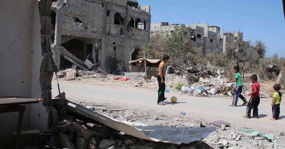 Crianças palestinas jogam bola perto dos destroços de casas em Khan Yunis, em Gaza, nesta quinta-feira (11).  A Human Rights Watch acusou Israel de cometer crimes de guerra ao atacar três escolas das Nações Unidas na Faixa de Gaza durante os combates de julho e agosto, matando civis palestinos que buscaram abrigo lá