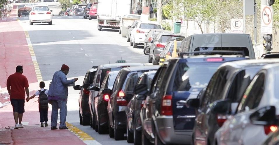 11.set.2014 - Pedestres desembarcam de carros em trecho da ciclovia Pacaembu na rua Piauí, em Higienópolis, zona central de São Paulo. Em vários trechos, carros invadem a ciclovia em conversões ou para acessar garagens, às vésperas da inauguração do novo trecho de ciclovias em São Paulo