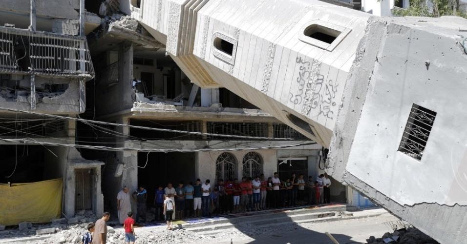 12.set.2014 - Muçulmanos palestinos fazem orações embaixo de escombros de mesquita na cidade de Gaza. O local foi destruídos durante os últimos conflitos entre o Exército de Israel e militantes do Hamas