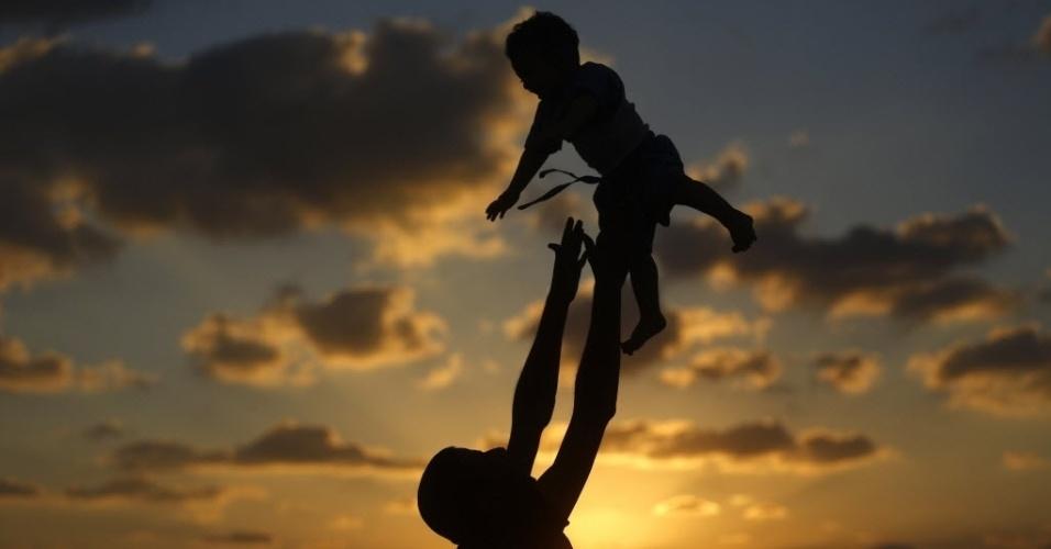12.set.2014 - Um palestino joga um menino pra cima enquanto eles tomam banho em uma praia na Cidade de Gaza, em nesta sexta-feira (12). Desde o dia 26 de agosto, Israel e o movimento islâmico Hamas, que domina Gaza, mantêm uma trégua para acabar na guerra que já matou mais de 2.200 pessoas