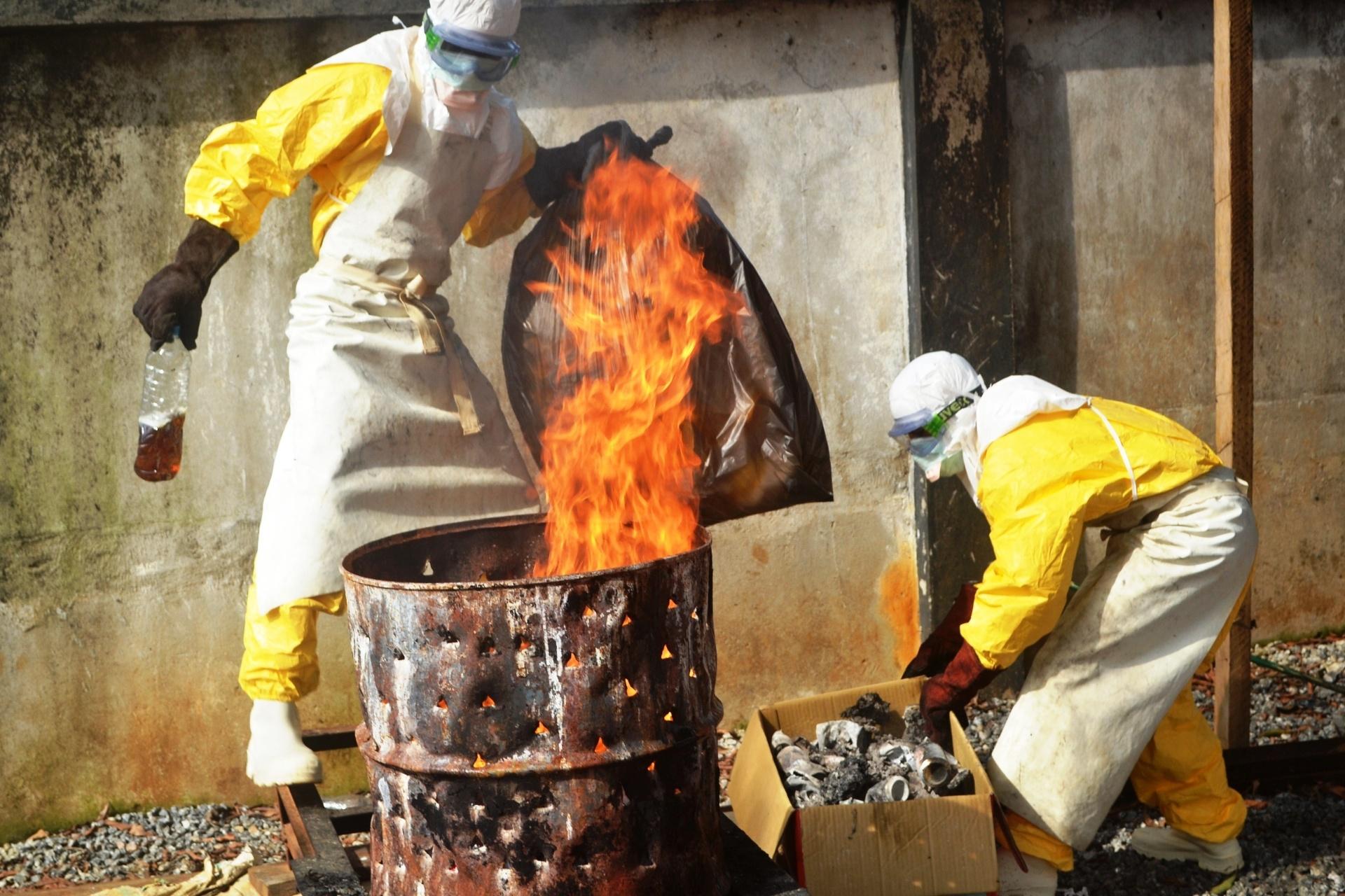 13.set.2014 - Trabalhadores de saúde queimam equipamentos de proteção usados na ONG Médicos Sem Fronteiras em Conacri, capital da Guiné, neste sábado (13). Especialistas em doenças infecciosas estão preocupados que o vírus ebola possa mutar e passar a ser transmitido pela tosse ou pelo espirro