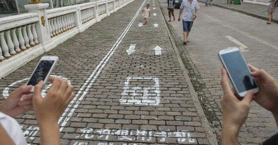 15.set.2014 - A cidade de Chongqing, China, ganhou uma faixa para quem digita no celular enquanto anda pela calçada. Já na faixa ao lado é proibido usar o smartphone enquanto anda. Não há informações se a marcação é provisória, e faz parte apenas de uma campanha, ou se é definitiva